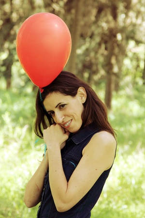 Beautiful woman with red balloon in the park photo