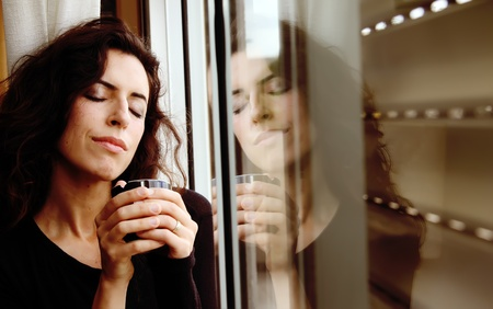 Photo of a beautiful young female drinking coffee and looking out the window photo