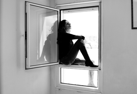 Portrait of beautiful woman sitting on the window Stock Photo - 19336449