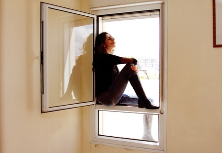 Portrait of beautiful woman sitting on the window Stock Photo - 19336478