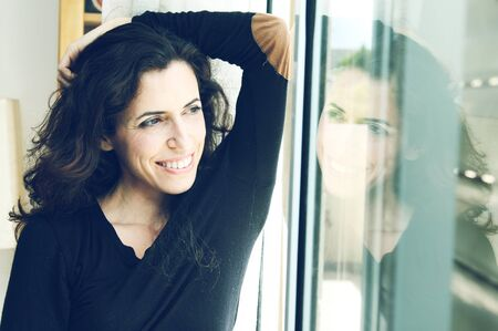 Beautiful 35 years old woman next to the window. Photo in old image style. Stock Photo - 19347325