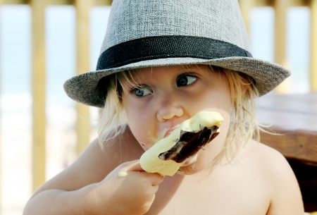 cute girl in the hat eating ice-cream photo