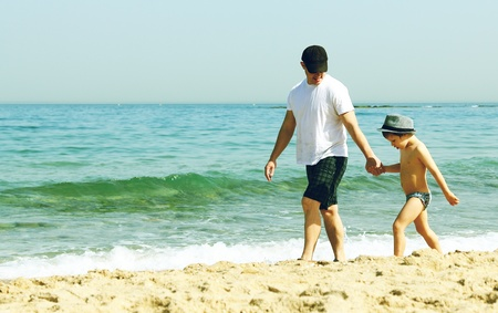 father and son walking together on the beach photo