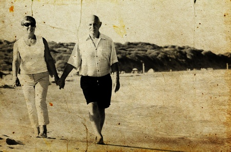 Happy senior couple walking together on a beach  Photo in old image style  photo