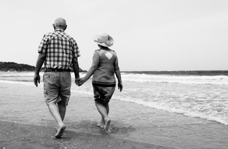 backview of senior couple walking on sandy beach Standard-Bild
