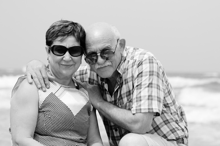 Happy elderly couple enjoying their retirement vacation near the sea photo
