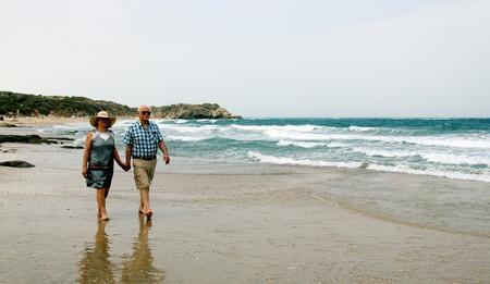 Happy elderly couple enjoying their vacation near the sea photo