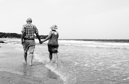 active woman: Happy senior couple walking together on a beach