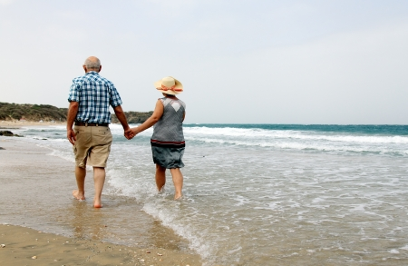 seniors: Happy senior couple walking together on a beach
