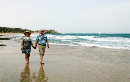 Happy elderly couple enjoying their vacation near the sea photo