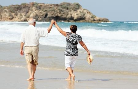 幸せな先輩カップルのビーチに一緒に歩いて