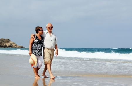 two year old: Happy senior couple walking together on a beach