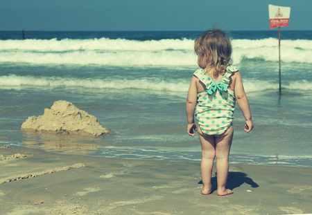 little girl on blue sea shore in summer vacation photo