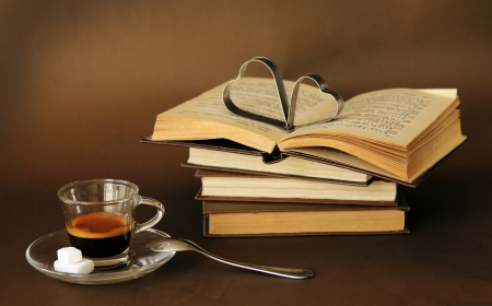 cup of coffee next to vintage books photo