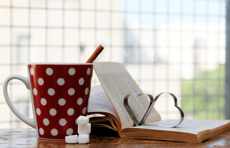 cup ofcoffee and book on wooden vintage table photo