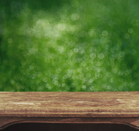 Vintage wooden table with foliage bokeh background photo