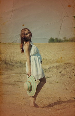 Young woman enjoying her pregnancy in the countryside. Photo in old image style.  photo