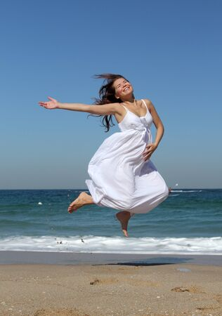 beautiful pregnant woman jumping on the beach photo