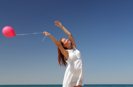 Breautiful girl with red balloon at blue sky background photo