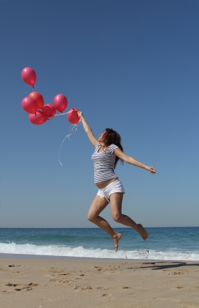 Beautiful girl with red balloons at blue sky background photo