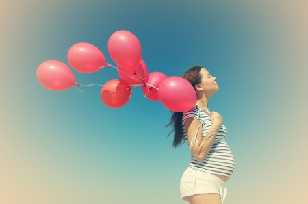 Young pregnant woman holding red balloons. Photo in old color image style. photo