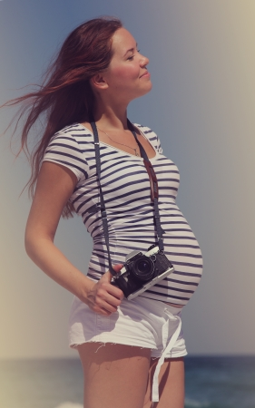 Young pregnant woman holding vintage camera. Photo in old color image style. photo