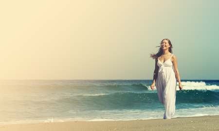 Young pregnant woman walking at the beach photo