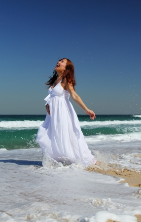 Young smiling woman in white dress standing in sea waves photo