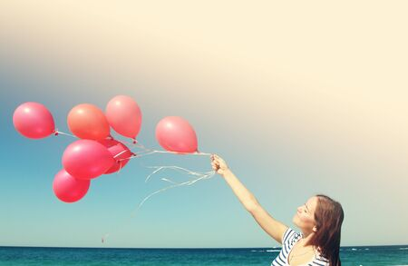 Young woman holding red balloons. Photo in old color image style. photo