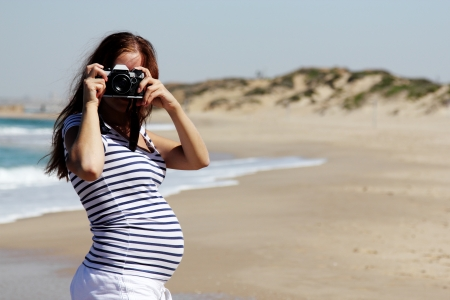 woman freedom: Young pregnant woman holding vintage camera