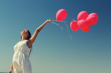 Junge schwangere Frau mit roten Luftballons. Foto im alten Stil Farbbild.