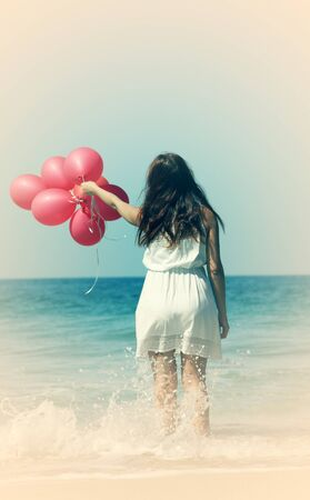 Young pregnant woman holding red balloons photo