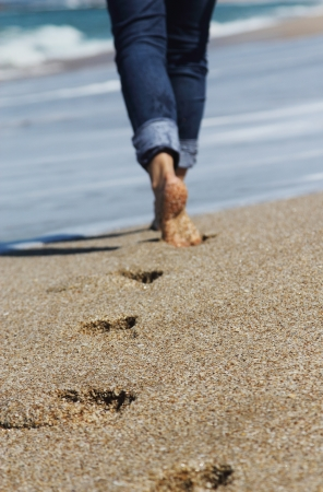 Young woman walking at the beach. Focus on the sand.