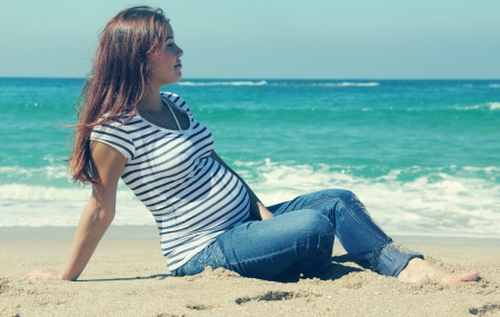 beautiful pregnant woman sitting on the beach photo