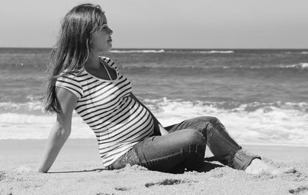 beautiful pregnant woman sitting on the beach photo