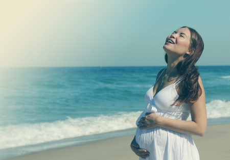 woman beach dress: Young pregnant woman walking on the beach Stock Photo