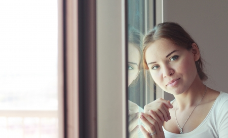 worried woman: beautiful woman stands in front of the window