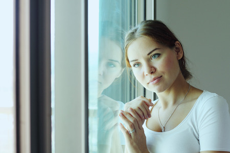 beautiful woman stands in front of the window photo