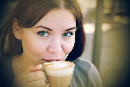 young girl with a cup of coffee. Focus on the eyes photo