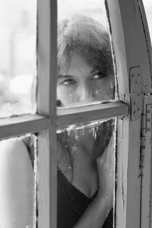 Art portrait of a beautiful young sadly girl looking through the window photo