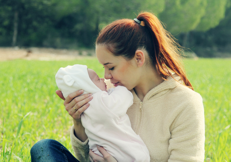 young mother with her newborn baby outdoor photo