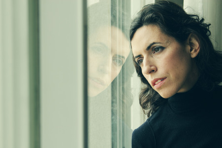 emotional grief: beautiful 35 year old woman stands in front of the window