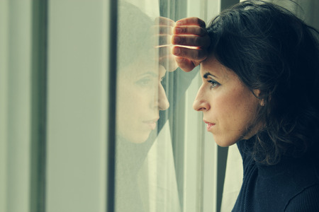 schöne 35-jährige Frau steht vor dem Fenster Lizenzfreie Bilder