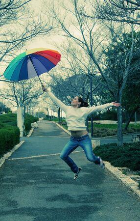 rainbow umbrella: Young woman jumpimg with big rainbow umbrella Stock Photo