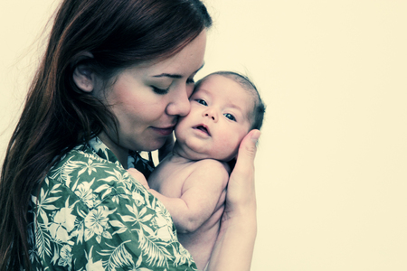 cradling: young mother with her baby. Photo in old image style