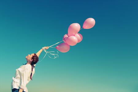 젊은 빨간 머리 여자 분홍색 풍선을 들고