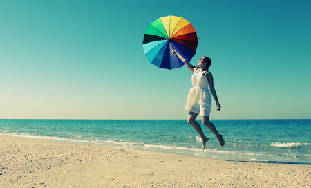 Summer vacation concept: beautiful model holding umbrella and posing at the seaside photo