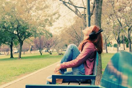 auriculares: Mujer joven hermosa con auriculares al aire libre