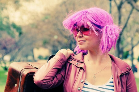 beautiful young woman with pink sunglasses and purple hair standing in the city park photo