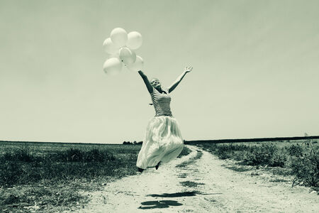 Young woman holding pink balloons and flying over a meadow.  photo